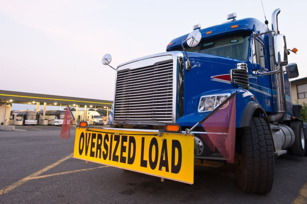truck with oversized load sign parked on the side of the road
